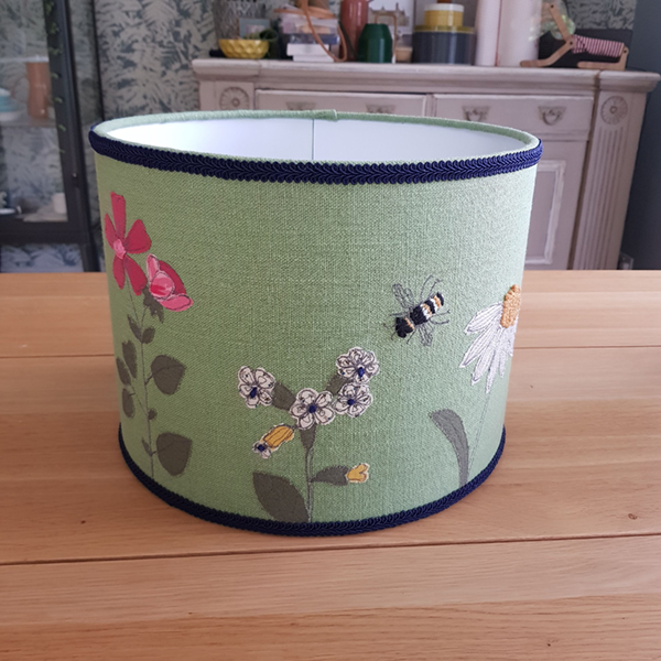 Green linen lampshade with embroidered flowers and bee